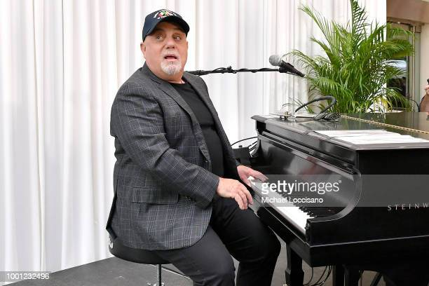 Billy Joel sits at a piano that was dedicated to him during an event at a press conference honoring his 100th Lifetime Performance at Madison Square...