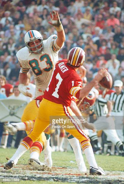 Billy Kilmer of the Washington Redskins drops back to pass under pressure from Vern Den Herder of the Miami Dolphins during Super Bowl VII at the Los...