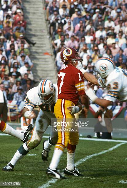 Billy Kilmer of the Washington Redskins drops back to pass under pressure from Vern Den Herder and Bill Stanfill of the Miami Dolphins during Super...