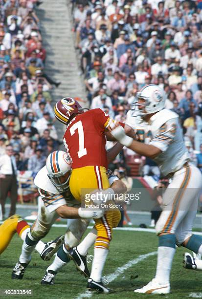 Billy Kilmer of the Washington Redskins gets his pass off under pressure from Vern Den Herder of the Miami Dolphins during Super Bowl VII at the Los...