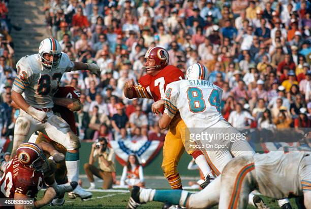 Billy Kilmer of the Washington Redskins gets his pass off under pressure from Vern Den Herder and Bill Stanfill of the Miami Dolphins during Super...