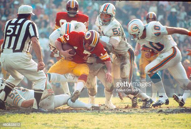 Billy Kilmer of the Washington Redskins gets sacked by Mike Kolen of the Miami Dolphins during Super Bowl VII at the Los Angeles Memorial Coliseum in...