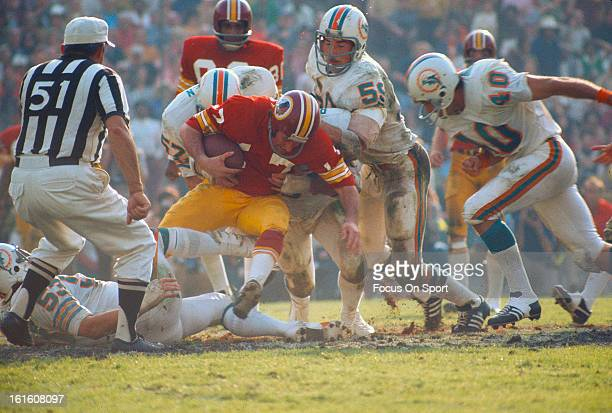 Billy Kilmer of the Washington Redskins gets tackled by Mike Kolen of the Miami Dolphins during Super Bowl VII at the Los Angeles Memorial Coliseum...