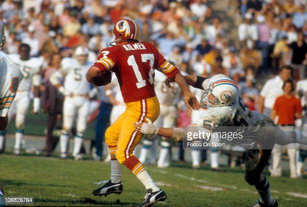 Billy Kilmer of the Washington Redskins tries to escape the grasp of Doug Swift of the Miami Dolphins during Super Bowl VII at the Memorial Coliseum...