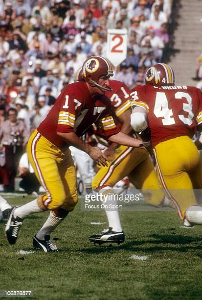 Billy Kilmer of the Washington Redskins turns to hand the ball off to running back Larry Brown against the Miami Dolphins during Super Bowl VII at...