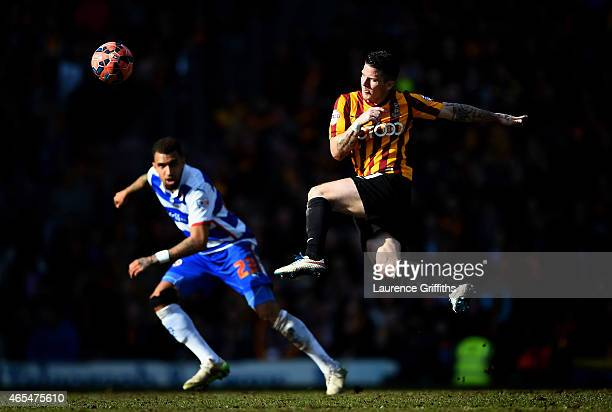 Billy Knott of Bradford City strikes the ball as Daniel Williams of Reading closes in during the FA Cup Quarter Final match between Bradford City and...