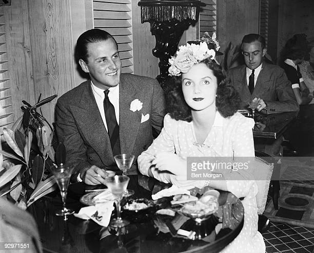 Billy Livingston and Brenda Frazier sitting at a table with cocktails c 1935