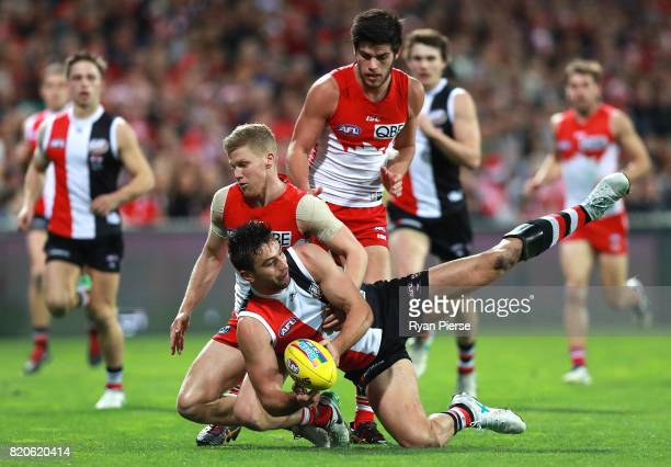 Billy Longer of the Saints is tackled by Dan Hannebery of the Swans during the round 18 AFL match between the Sydney Swans and the St Kilda Saints at...