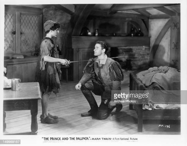 Billy Mauch placing sword on the shoulder of Errol Flynn in a scene from the film 'The Prince And The Pauper' 1937