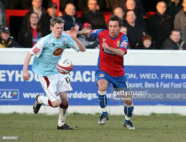 Billy McKay of Northampton Town challenges for the ball with Darren Currie of Dagenham Redbridge during the Coca Cola League Two Match between...