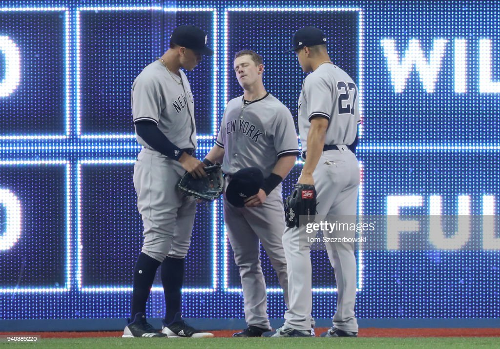 Billy McKinney #39 of the New York Yankees is examined by Aaron Judge #99 and Giancarlo Stanton #27 after crashing into the wall in the first inning during MLB game action against the Toronto Blue Jays at Rogers Centre on March 31, 2018 in Toronto, Canada.