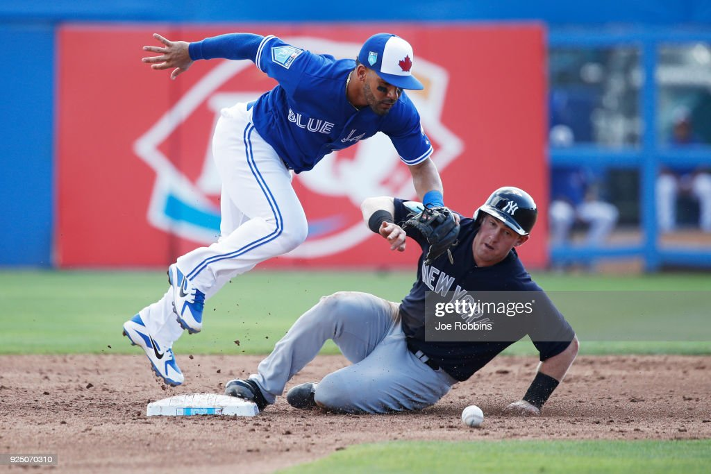 Billy McKinney #71 of the New York Yankees slides safely into second base after the ball was dropped by Devon Travis #29 of the Toronto Blue Jays in the third inning of a Grapefruit League spring training game at Florida Auto Exchange Stadium on February 27, 2018 in Dunedin, Florida.
