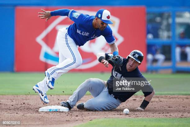 Billy McKinney of the New York Yankees slides safely into second base after the ball was dropped by Devon Travis of the Toronto Blue Jays in the...