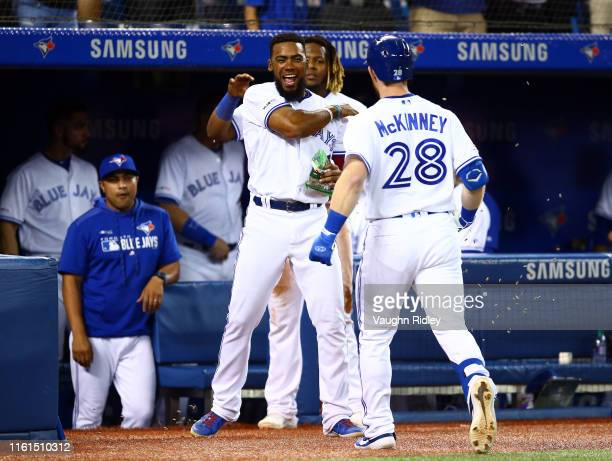 Billy McKinney of the Toronto Blue Jays hits a solo home run and celebrates with Teoscar Hernandez in the sixth inning during a MLB game against the...