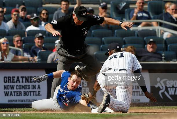 Billy McKinney of the Toronto Blue Jays is tagged out at third base in the sixth inning by Miguel Andujar of the New York Yankees as umpire Larry...