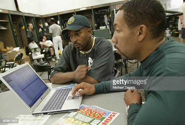 Billy McMillon and Clarence Cockrell of the Oakland Athletics look at a laptop computer before the MLB game against the Anaheim Angels at Network...