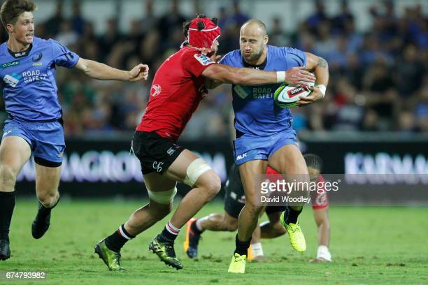 Billy Meakes of the Force tries to break free of a tackle from Warren Whiteley of the Lions during the round 10 Super Rugby match between the Force...