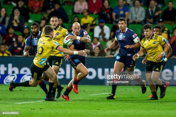 Billy Meakes of the Melbourne Rebels deflects a tackle from Beauden Barrett of the Wellington Hurricanes during Round 7 of the Super Rugby Series...