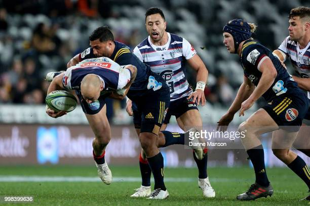 Billy Meakes of the Rebels is tackled by Lima Sopoaga of the Highlanders as Michael Ruru of the Rebels and James Lentjes of the Highlanders look on...