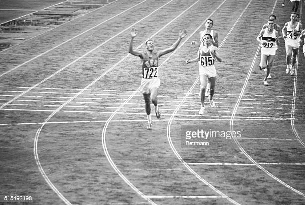 Billy Mills displays joy after crossing finish line winning 10,000 meter race in Olympic record time of 28:24.4. 2nd was Mohammed Gammoudi of Tunisia...