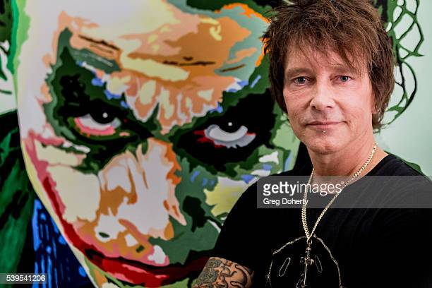 Billy Morrison poses for a picture in front of his painting of Heath Ledger as 'The Joker' at his VIP Reception of Mixed Messages A Brand New...
