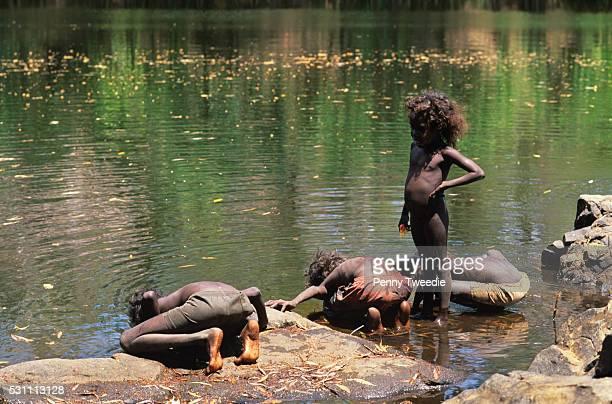 Billy Nalakandi's children drinking proper aboriginal way from the Mann River central Arnhem Land Aborigines believe it is much cleaner to drink...