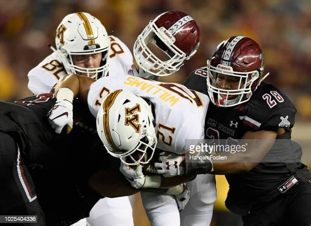 Billy Nipp of the New Mexico State Aggies loses his helmet as he and teammate Shane Jackson tackle Bryce Williams of the Minnesota Golden Gophers...