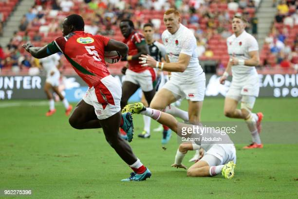 Billy Odhiambo of Kenya gets past Dan Bibby of England during the 2018 Singapore Sevens Pool B match between Kenya and England at National Stadium on...