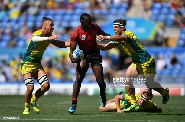 Billy Odhiambo of Kenya takes on Ben O'Donnell and Charlie Taylor of Australia during the Rugby Sevens Men's Placing 58th match between Australia and...
