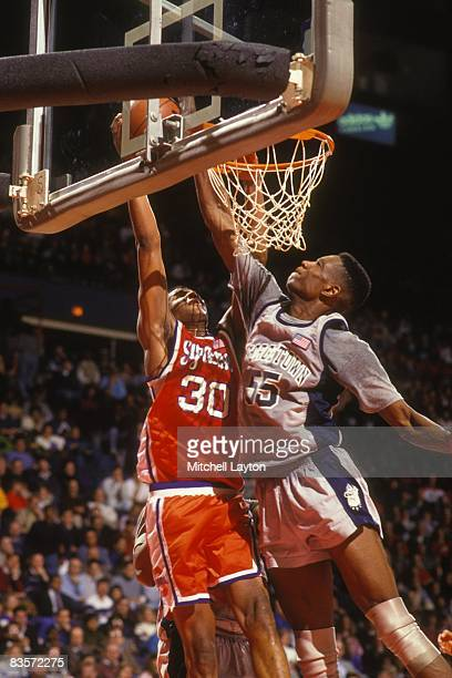 Billy Owens of the Syracuse Orangeman takes a shot over Dikembe Mutombo of the GEorgetown Hoyas during a college basketball game at Capitol Centre on...