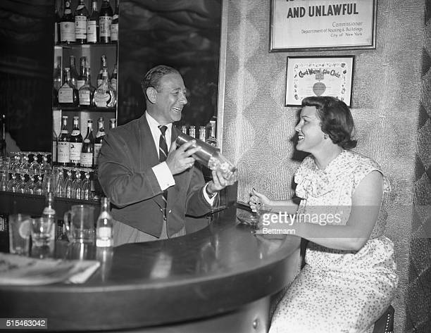Billy Reed owner of Billy Reed's little club tends bar At right is miss Fleda Angel of Los Angeles