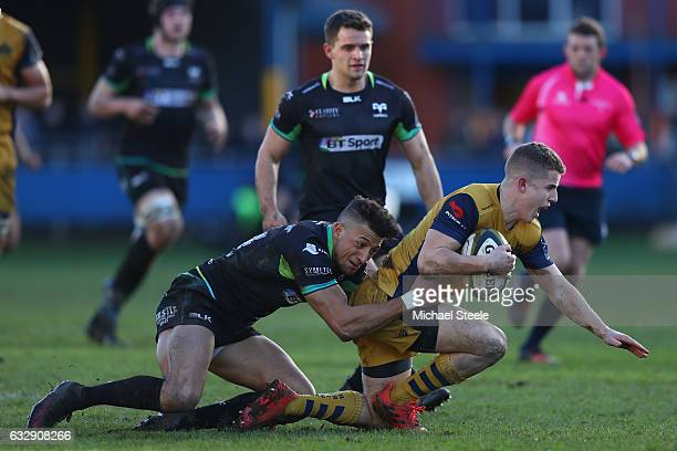 Billy Searle of Bristol is tackled by Jay Baker of Ospreys during the Anglo Welsh Cup match between Ospreys and Bristol Rugby at the Brewery Field on...