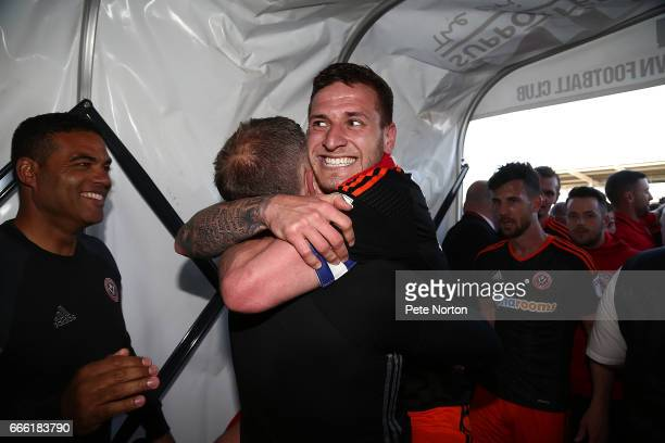 Billy Sharp of Sheffield United celebrates with manager Chris Wilder after promotion to the Championship after the Sky Bet League One match between...