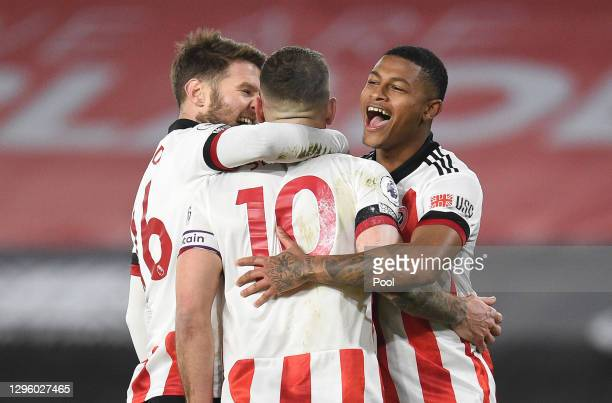 Billy Sharp of Sheffield United celebrates with Oliver Norwood and Rhian Brewster after scoring a penalty for his teams first goal during the Premier...