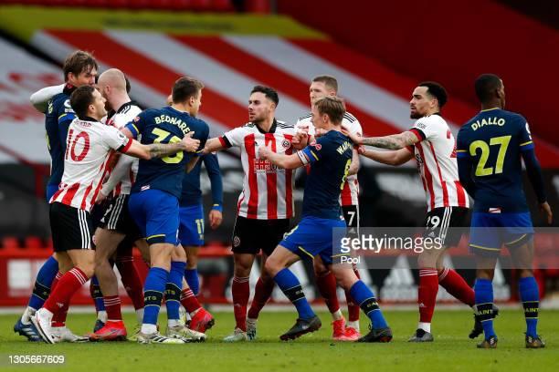 Billy Sharp of Sheffield United holds back Jan Bednarek of Southampton as Kean Bryan of Sheffield United holds back James Ward-Prowse of Southampton,...