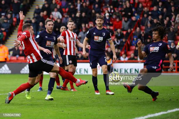 Billy Sharp of Sheffield United scores his team's first goal as Nathan Ake of AFC Bournemouth attempts to block during the Premier League match...