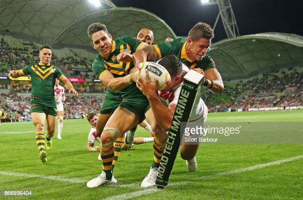 Billy Slater and Dane Gagai of the Kangaroos perform a try saving tackle as Ryan Hall of England attempts to score a try in the corner during the...