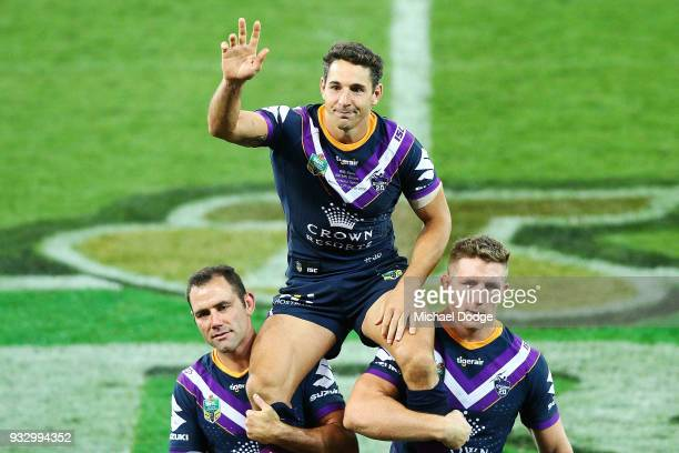 Billy Slater is carried off by Cameron Smith and Ryan Hoffman of the Storm after playing his 300th match during the round two NRL match between the...