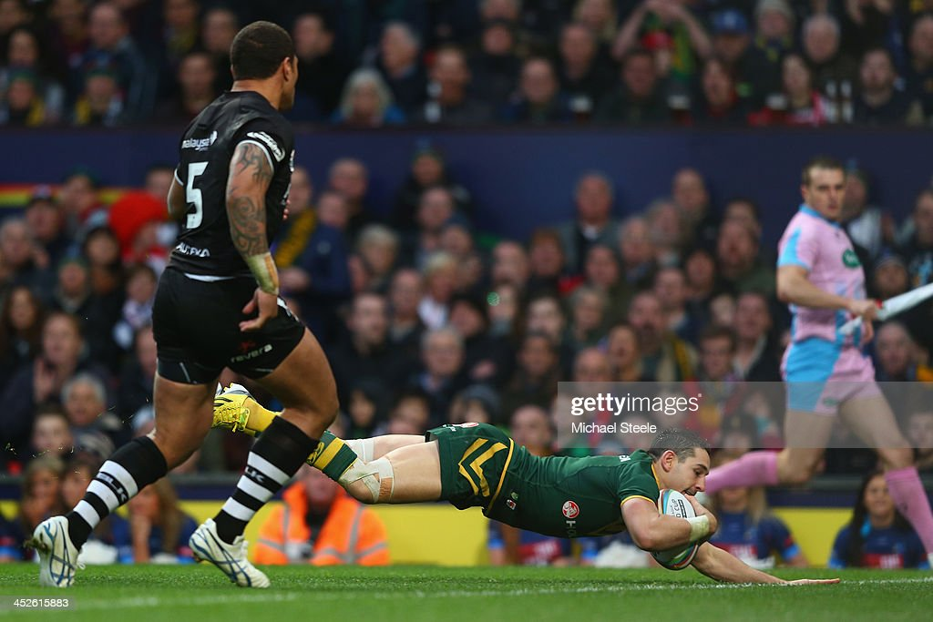 Billy Slater (R) of Australia scores his second try as Manu Vatuvei (L) of New Zealand looks on during the Rugby League World Cup Final between Australia and New Zealand at Old Trafford on November 30, 2013 in Manchester, England.