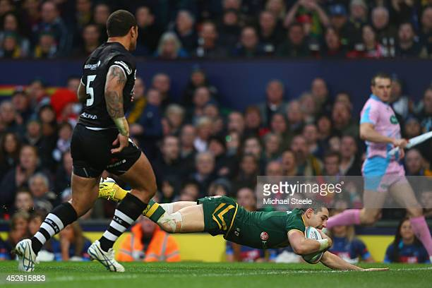 Billy Slater of Australia scores his second try as Manu Vatuvei of New Zealand looks on during the Rugby League World Cup Final between Australia and...