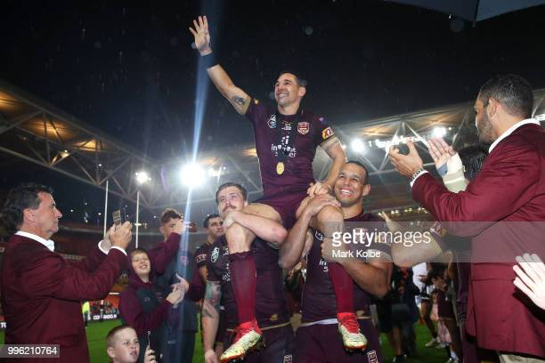Billy Slater of Queensland waves to the crowd as he is chaired from the field by Cameron Munster and Will Chambers of Queensland after his final game...