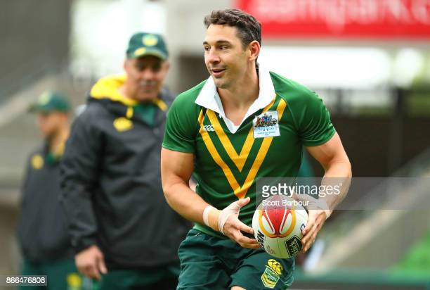 Billy Slater of the Kangaroos runs with the ball as Mal Meninga coach of the Kangaroos looks on during an Australian Kangaroos training session on...