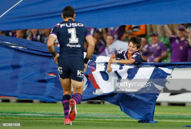 Billy Slater of the Melbourne Storm goes to help his son Jake as he gets stuck in the banner that celebrates Slaters 300th game during the round two...
