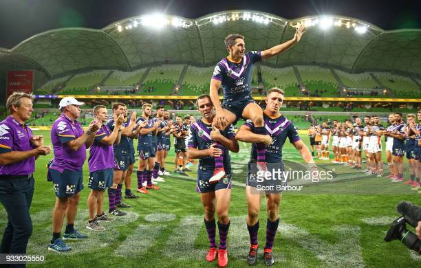 Billy Slater of the Melbourne Storm is chaired off by teammates Cameron Smith of the Melbourne Storm and Ryan Hoffman of the Melbourne Storm after...