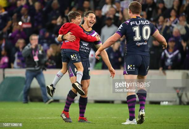 Billy Slater of the Melbourne Storm is congratulated by his son Jake and Tim Glasby of the Melbourne Storm at the full time siren during the NRL...