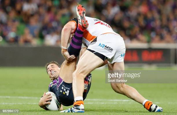 Billy Slater of the Melbourne Storm is tackled during the round two NRL match between the Melbourne Storm and the Wests Tigers at AAMI Park on March...