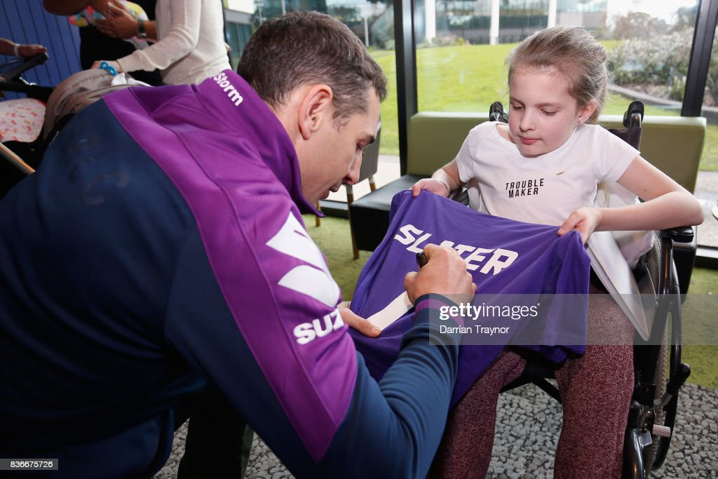 Billy Slater of the Melbourne Storm signs an autograph for 12 year old Courtney Keel during a Melbourne Storm NRL media opportunity at the Royal Children's Hospital on August 22, 2017 in Melbourne, Australia.
