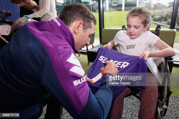 Billy Slater of the Melbourne Storm signs an autograph for 12 year old Courtney Keel during a Melbourne Storm NRL media opportunity at the Royal...