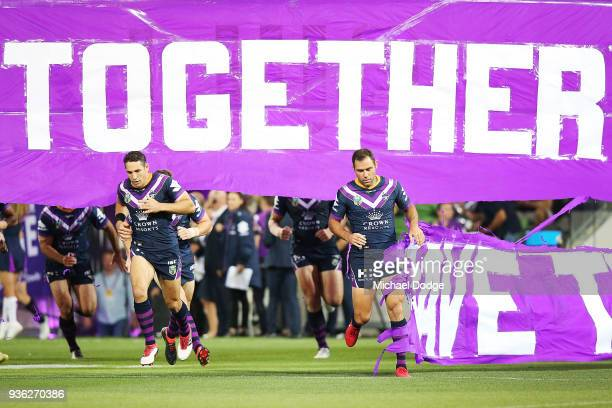 Billy Slater of the Storm and Cameron Smith run through the banner during the round three NRL match between the Melbourne Storm and the North...
