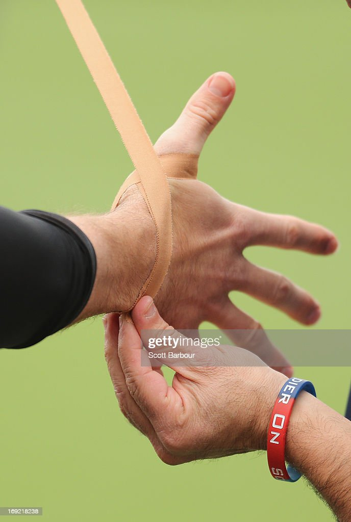 Billy Slater of the Storm has his hand taped up by a trainer during a Melbourne Storm NRL training session at Gosch's Paddock on May 22, 2013 in Melbourne, Australia.